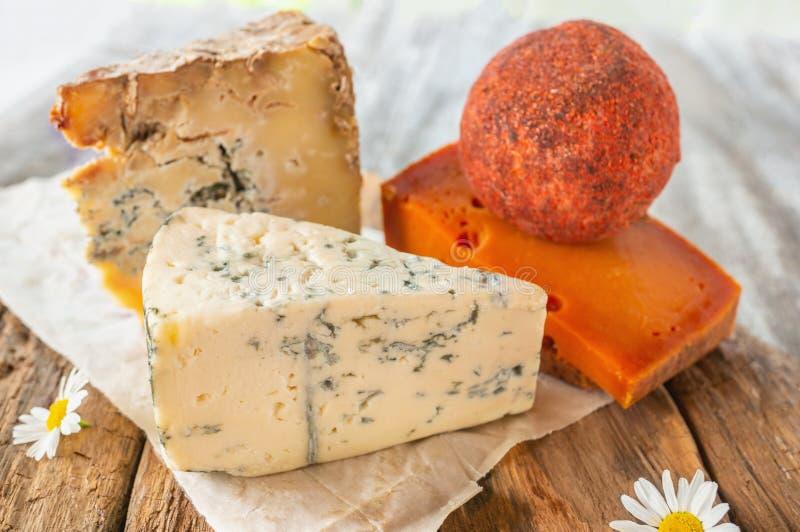 Quesos picantes de la charcutería de diversas variedades Cheddar rojo, azul de Dor, Stilton, loma de Belper en un de madera textu imágenes de archivo libres de regalías