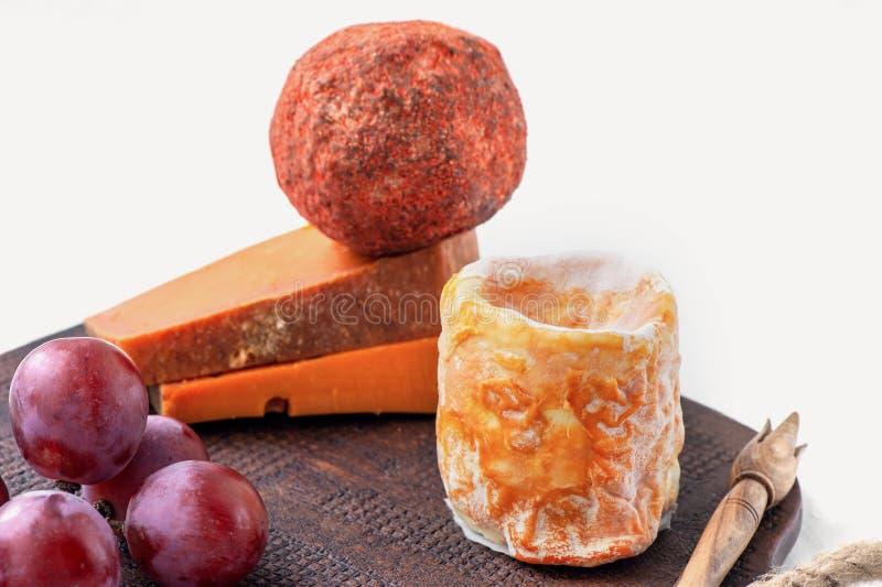 Quesos picantes de la charcutería de diversas variedades Cheddar rojo, Dor azul, pirámide, Stilton, Belper-Noll en un tablero de  foto de archivo