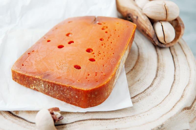 Quesos picantes de la charcutería El Cheddar rojo, en un fondo de madera texturizado hermoso con las nueces de pacana es un bocad fotos de archivo