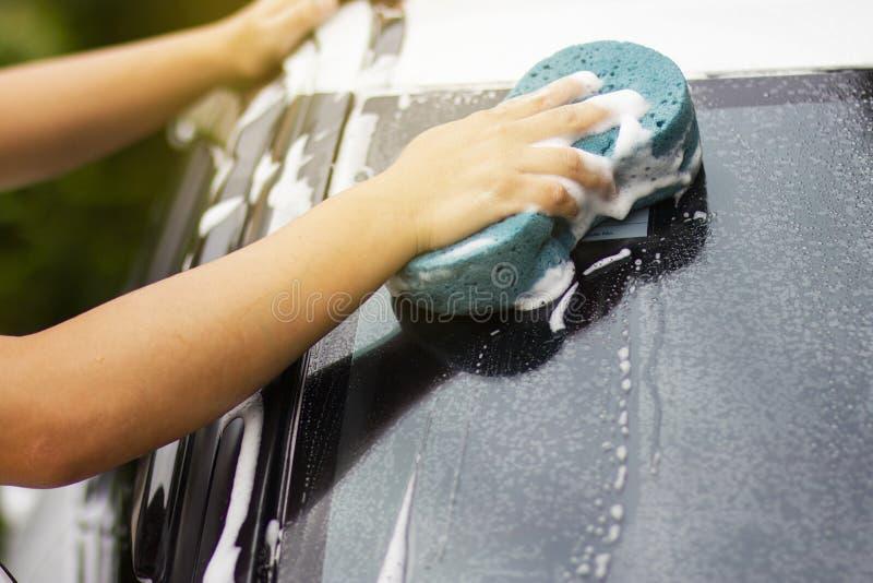 Questa immagine ? un'immagine di pulitura dell'automobile con un panno blu del microfiber a mano Concetto dell'autolavaggio fotografia stock libera da diritti