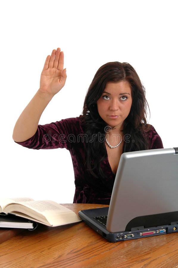 Question. A young woman at her desk raising her hand with a question stock photos