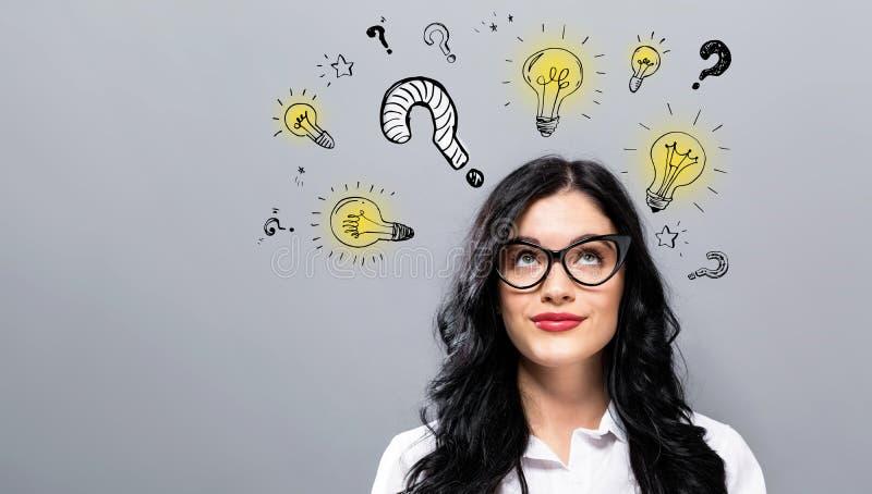 Question avec les ampoules avec la jeune femme d'affaires images libres de droits