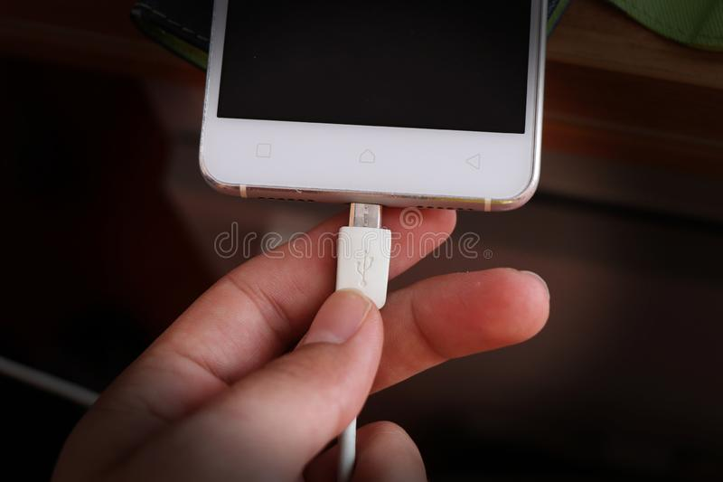 Question of energy in real time. White smartphone gets to starts of charge. Man holds white cabel and tries hit the hole from the. Phone stock images