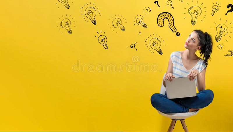 Question with light bulbs with woman using a laptop. Question with light bulbs with young woman using a laptop computer royalty free stock photos