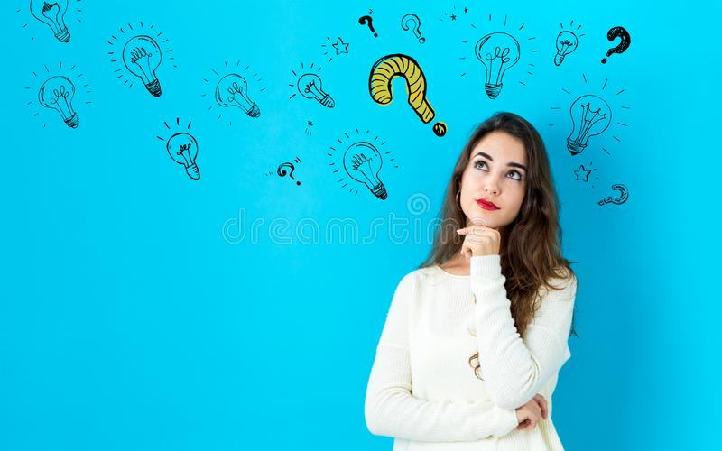 Question with light bulbs with young woman stock image