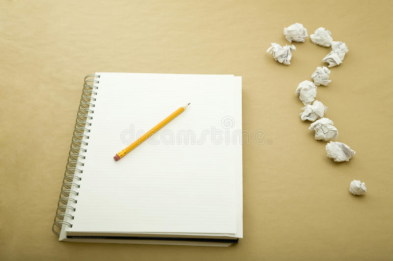 Question mark. A pencil on notebook and a question mark royalty free stock image