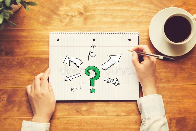 Question mark with arrows with a person holding a pen royalty free stock photography