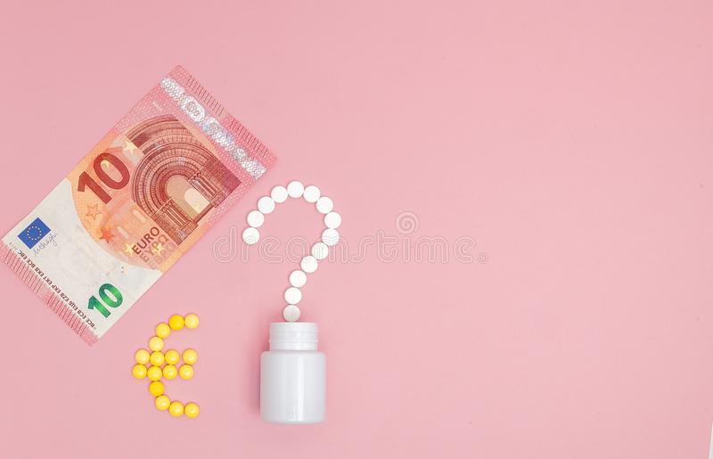 A question mark and euro mark laid out of pills and 10 euro on a pink background. Concept of medicine, money and health royalty free stock image