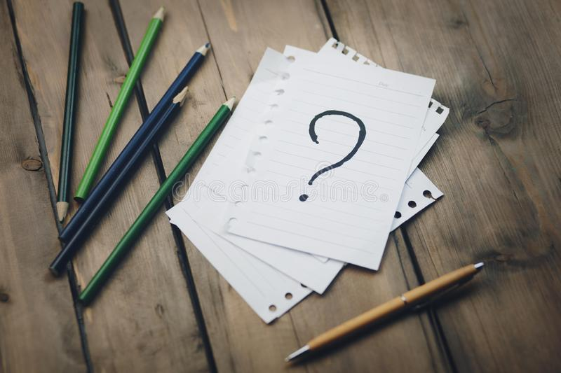 Question mark on notebook. And colorful pencils on table royalty free stock photos
