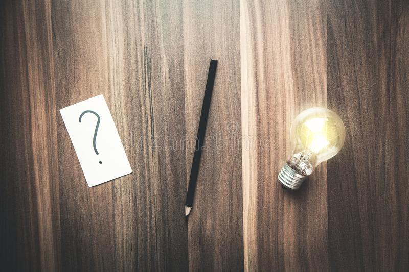 Question mark in paper with pencil and light bulb on a wood back royalty free stock image