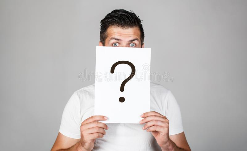 Question mark, symbol. Pensive male. Man a question. Doubtful man holding Question Mark. Problems and solutions. Getting stock photography