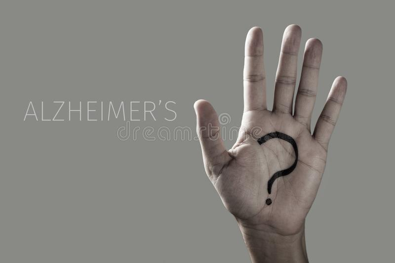 Question mark and text alzheimers. Man with a question mark painted in the palm of his hand and the text alzheimers on an off-white background stock photography