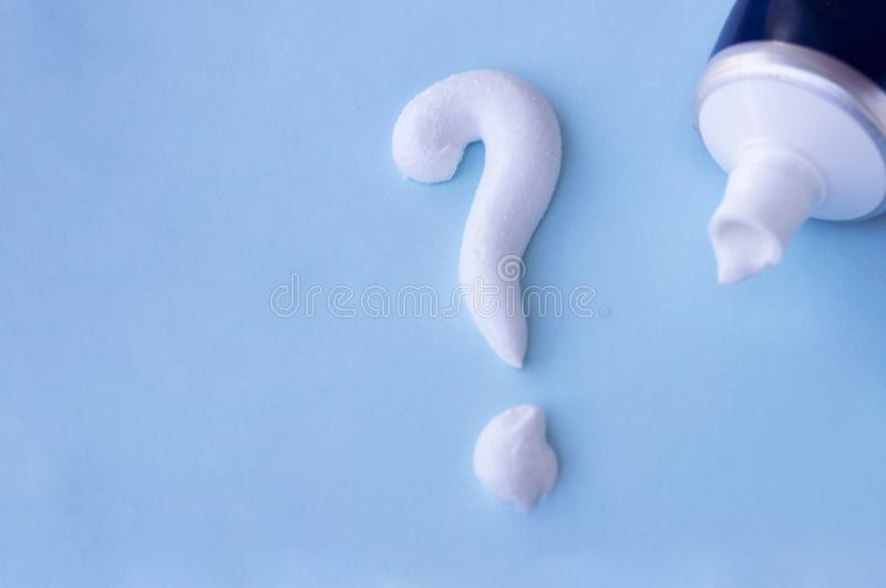 Question mark from toothpaste on blue background, toothpaste selection concept.  stock photography