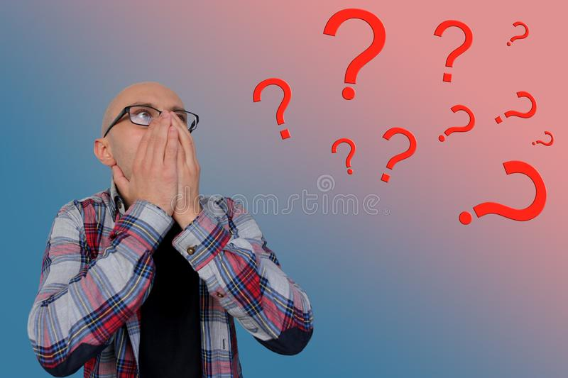 Question marks around a young man with glasses covering his face with his hands, psychological concept stock photography