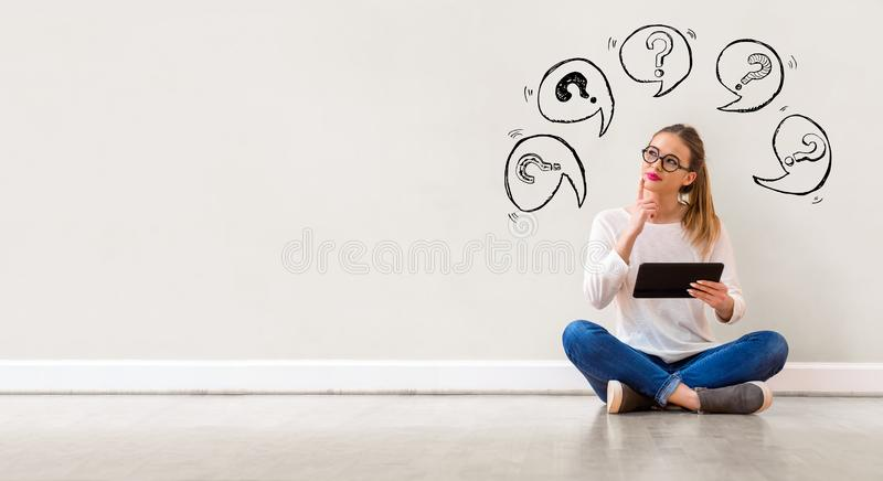 Question marks with speech bubbles with woman using a tablet royalty free stock photo