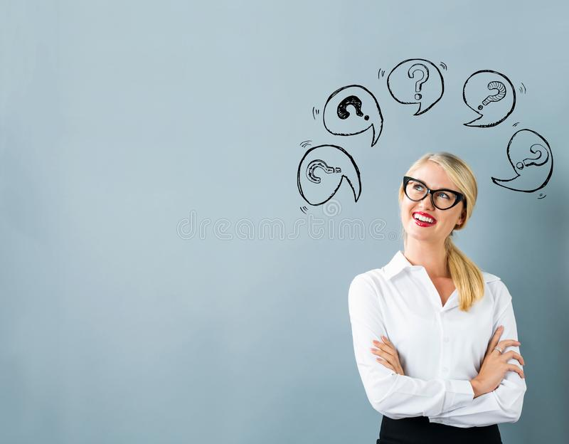 Question marks with speech bubbles with young woman stock image