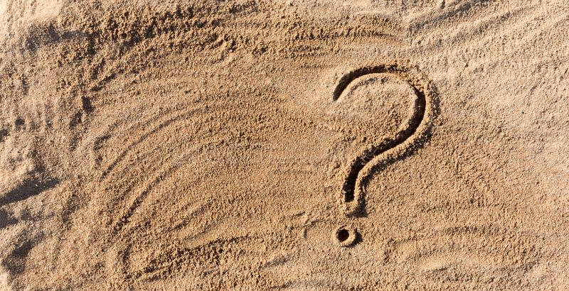 Question marks written on beach sand close up, with copy space royalty free stock photos