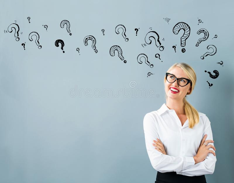 Question marks with young woman stock photography