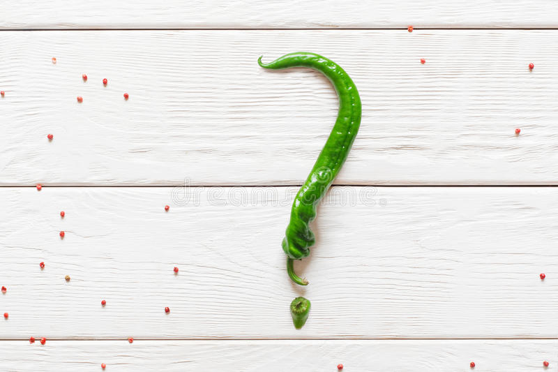 Question sign made from green chili. Unusual form of hot pepper. Kitchen, food, menu, diet, secret, mystery concept royalty free stock photo