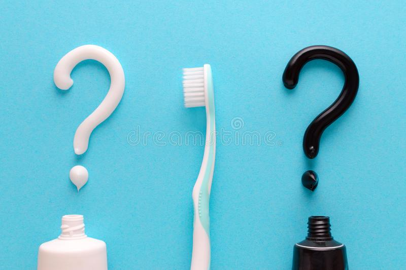 Question from white and black toothpaste, teeth care concept, toothbrush on blue background. Flatlay royalty free stock photos