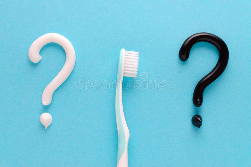 Question from white and black toothpaste, teeth care concept, toothbrush on blue background. Flatlay royalty free stock photo