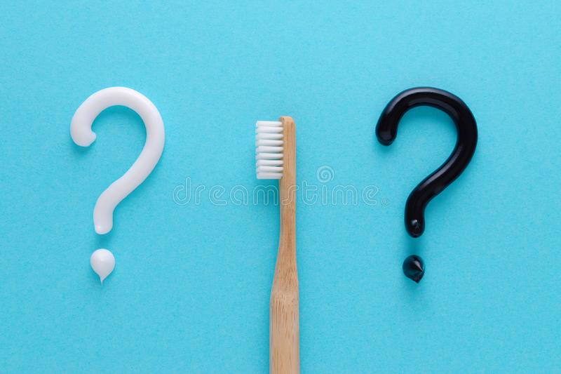 Question from white and black toothpaste, teeth care concept, wooden toothbrush on blue background. Flatlay royalty free stock images
