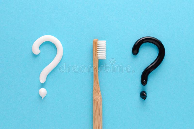 Question from white and black toothpaste, teeth care concept, wooden toothbrush on blue background. Flatlay stock images