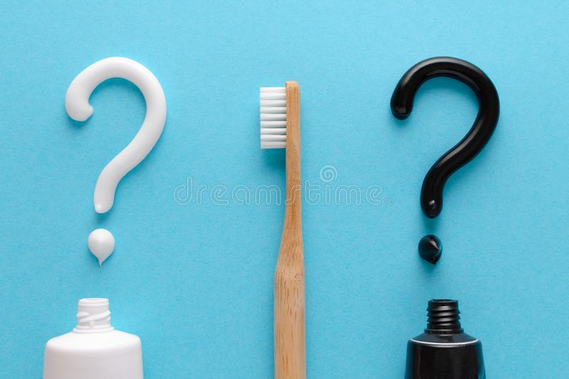 Question from white and black toothpaste, teeth care concept, wooden toothbrush on blue background. Flatlay stock photos