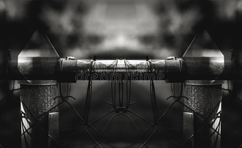 Questionably Safe and Secure. Black and white closeup shot of a section of chain link fence being held to the support rail by bailing wire wrapped around the royalty free stock photography
