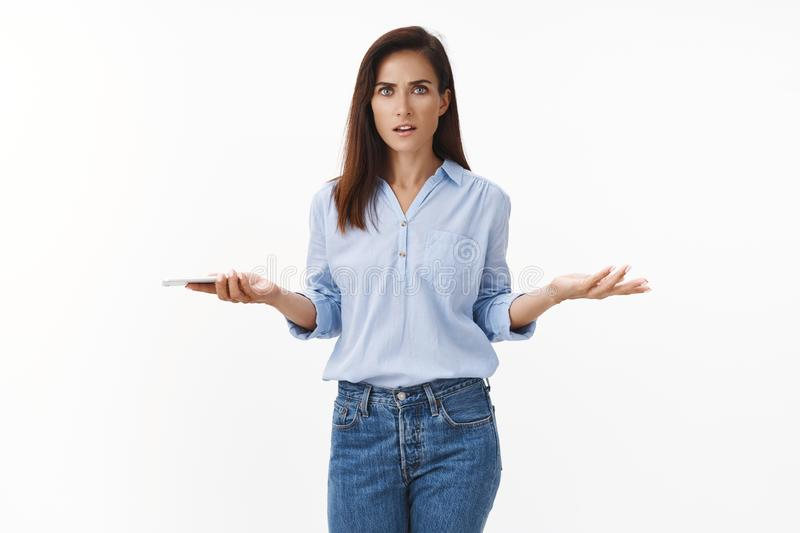 Questioned disappointed adult businesswoman complain employees, receive bad news via text message, hold smartphone. Spread hands sideways dismay, stare camera royalty free stock photography