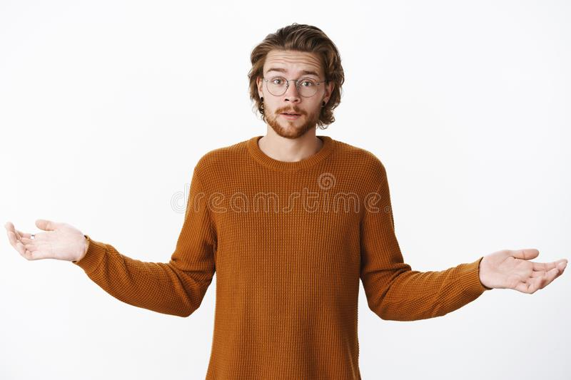 Questioned guy standing with raised eyebrows and hands sideways as shrugging wanna hear explanations being confused and. Frustrated with strange behaviour stock photo