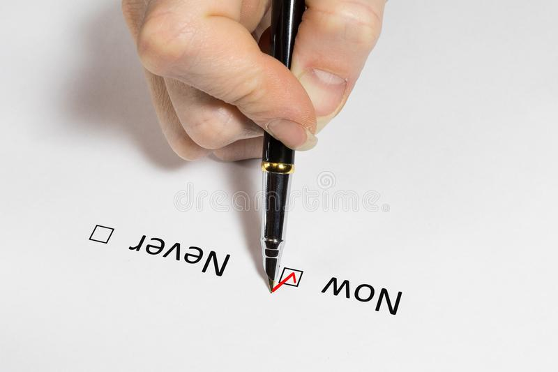 Question. Make a decision now or never. Red checkmark on white paper. stock photo