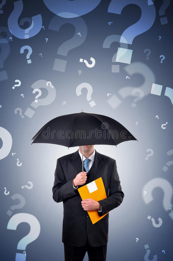 Questions. Businessman is holding an umbrella, question marks falling from the sky stock photo