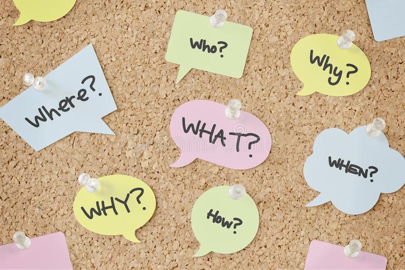 Questions speech bubbles on pinboard. Questions speech bubbles on cork pinboard royalty free stock photos