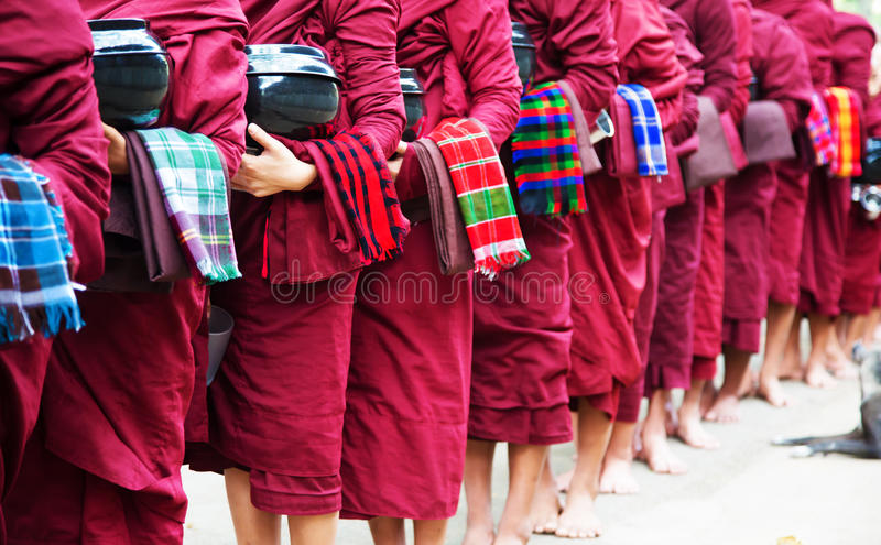 Queue of buddhist monks to get meal, Myanmar. All of them have a bowl and a napkin in their hands stock photo