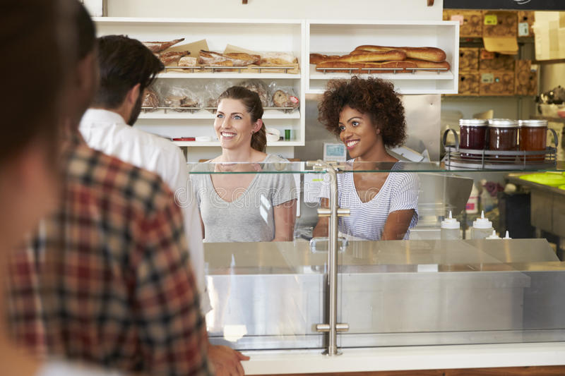 A queue of customers served by two women at a sandwich bar royalty free stock photo