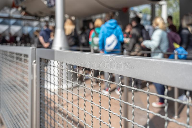 Queue in a park with a security fence. Focus on the fence with staggered perspective stock photography