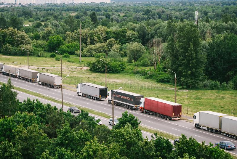 Queue of trucks passing the international border, red and different colors trucks in traffic jam on the road. Top view royalty free stock image