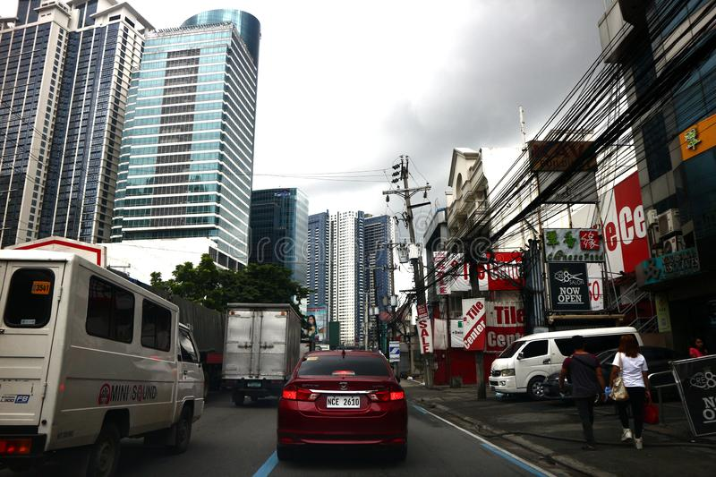 Cars and other vehicles pass commercial establishments along a traffic congested road. QUEZON CITY, PHILIPPINES – AUGUST 24, 2019: Cars and other vehicles royalty free stock photos