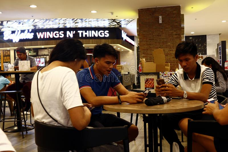 Customers use their smartphone while waiting for their food at a food court. QUEZON CITY, PHILIPPINES – AUGUST 25, 2019: Customers use their smartphone royalty free stock photos