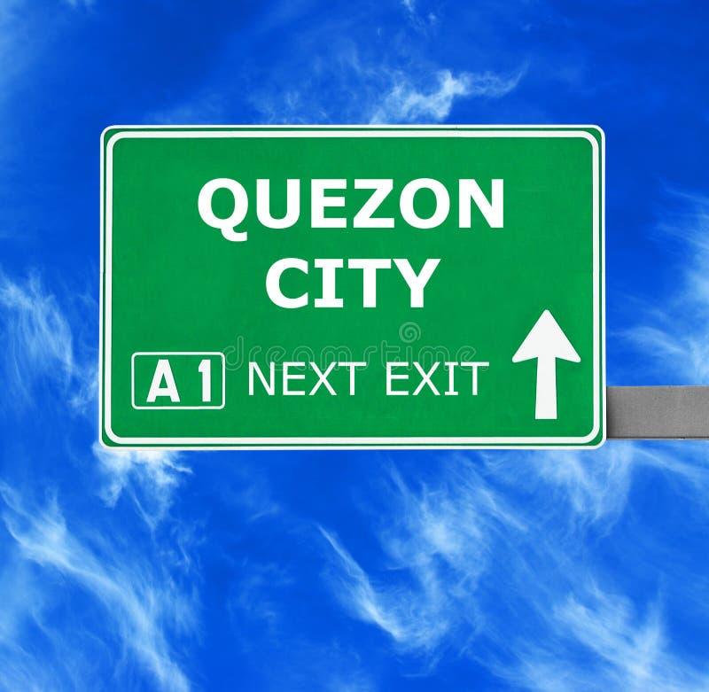 QUEZON-STADSverkeersteken tegen duidelijke blauwe hemel stock afbeeldingen