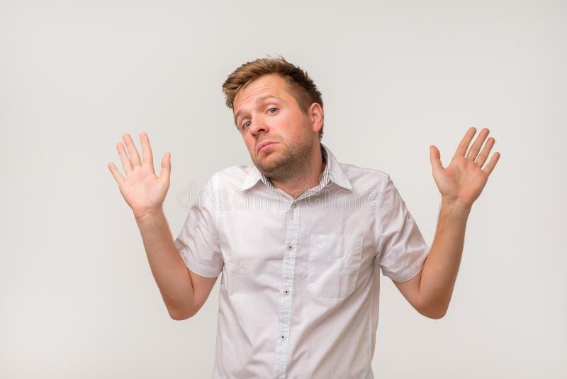 Quién sabe No es yo Hombre caucásico desconcertado en la camisa blanca no seguro foto de archivo libre de regalías