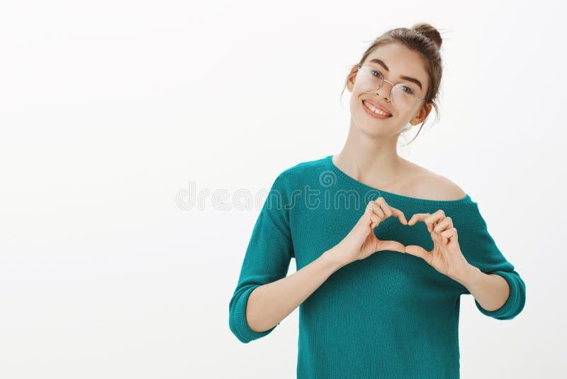 Quiérale querido Retrato de la mujer caucásica linda y blanda en vidrios y suéter flojo, cabeza inclinable y sonrisa foto de archivo