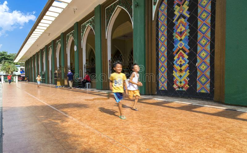 Quiapo, Φιλιππίνες - 16 Ιουλίου 2016: Αγόρια που τρέχουν κοντά στο χρυσό μουσουλμανικό τέμενος στοκ εικόνα