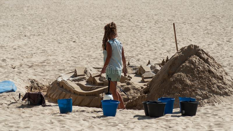 Portrait of woman building an artistic sand castle on the beach royalty free stock photo