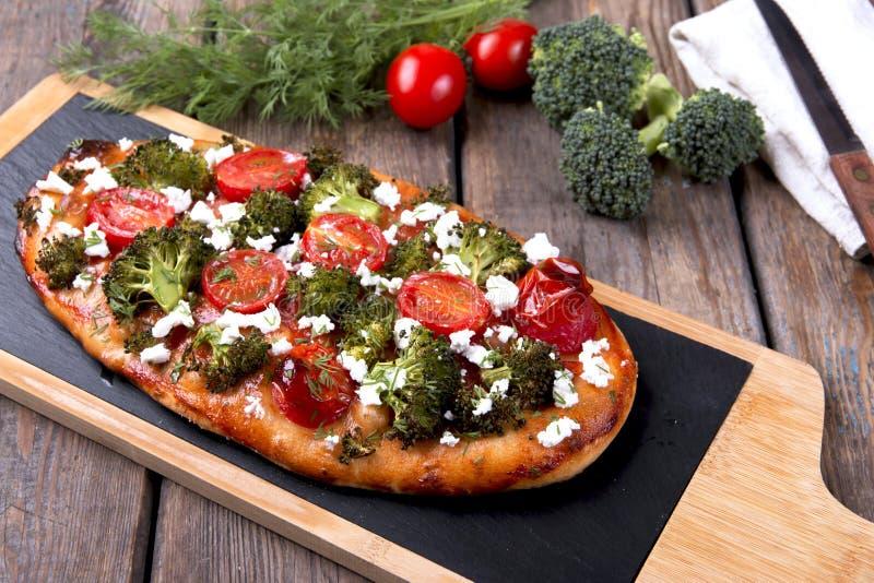 quiche agria con el tomate del bróculi y el queso de cabra imagen de archivo
