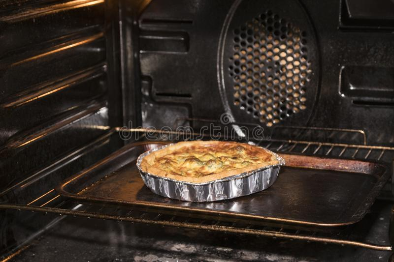 Quiche baking in an oven royalty free stock image