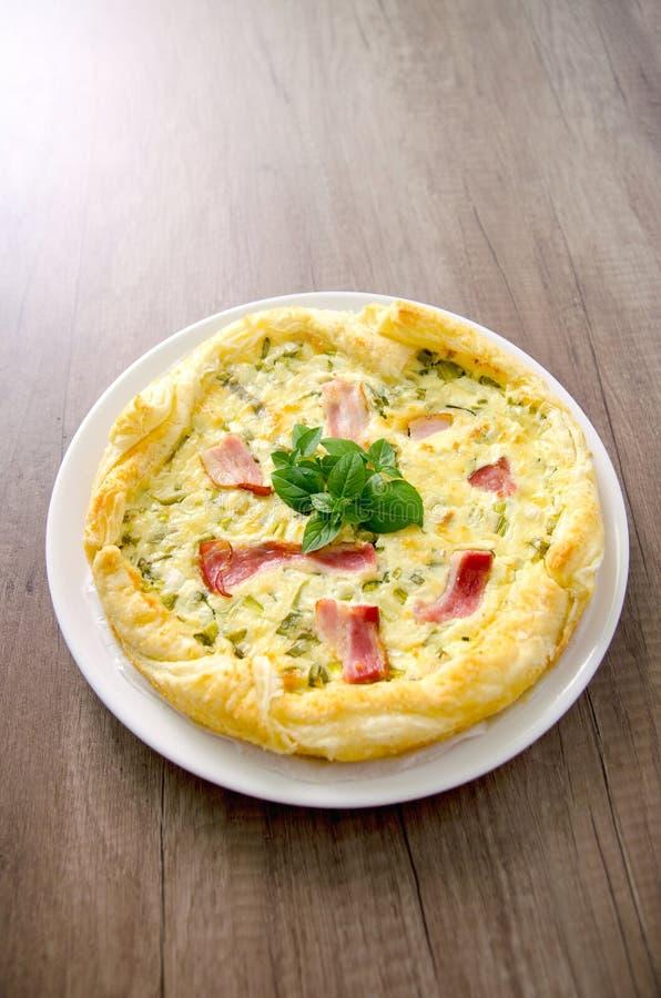 Quiche casalinga dell'uovo del bacon e degli spinaci in una crosta di torta sul bordo di legno Cucina francese immagine stock libera da diritti