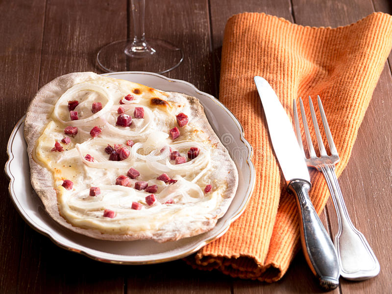 Quiche with onions and bacon. Quiche on a wooden tray royalty free stock image