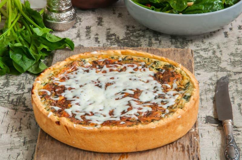 A quiche recentemente cozida com queijo e creme dos espinafres serviu na imagem de stock